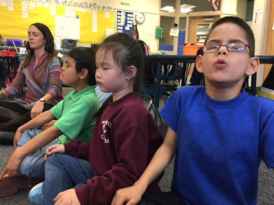 First-graders at Denver's Munroe Elementary do a mindfulness exercise led by school psychologist Amy Schirm. (Ann Schimke/Chalkbeat)