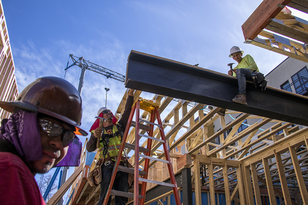 Rolando Padilla (left to right), Franklin Munguia and Yerlin Ernandez work on a condo construction site in West Highland, April 18, 2018. (Kevin J. Beaty/Denverite)