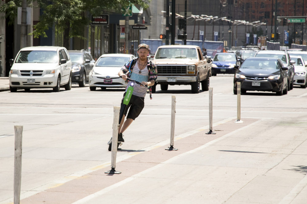 A man weaves between pylons on a Lime electric scooter, June 12, 2018. (Kevin J. Beaty/Denverite)