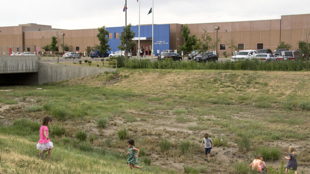 Kids play in front of the GEO private immigrant detention facility in Aurora as protesters speak out against child separations in immigration cases, June 14, 2018. (Kevin J. Beaty/Denverite)