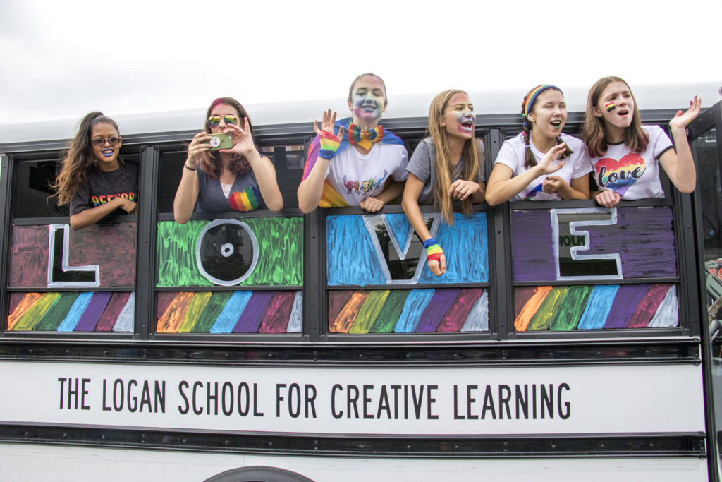Students from the Logan School for Creative Learning hang out of a bus in the Denver PrideFest parade, June 17, 2018. (Kevin J. Beaty/Denverite)