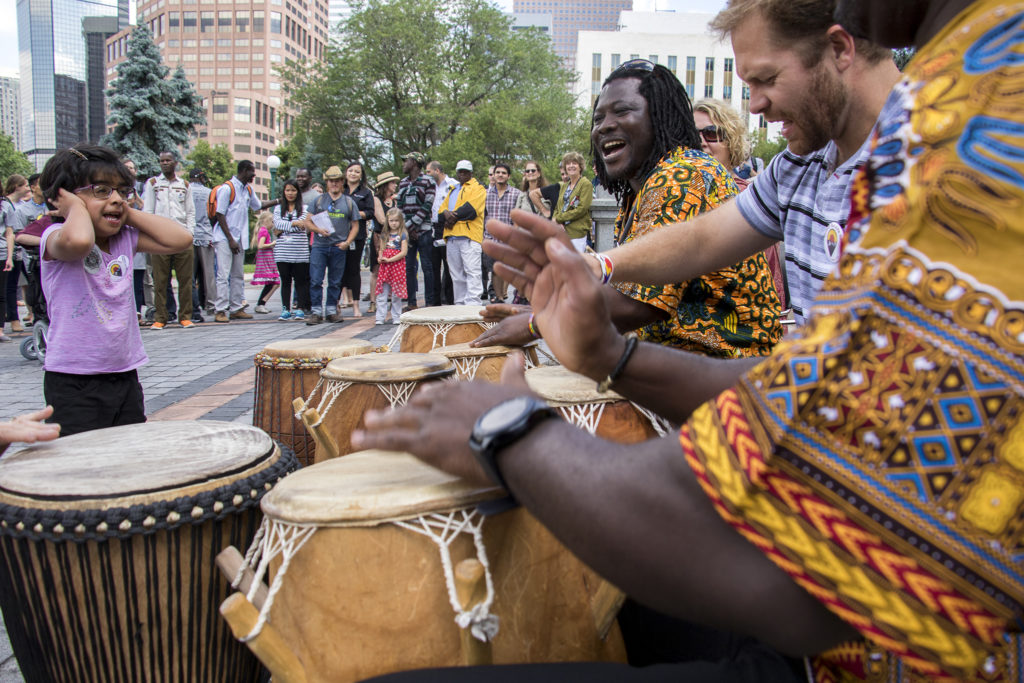 Jimmy Vaughn (right to left), Nii Okai Aryeetey play drums during the 2018 World Refugee Day celebration on the Capitol steps. (Kevin J. Beaty/Denverite)