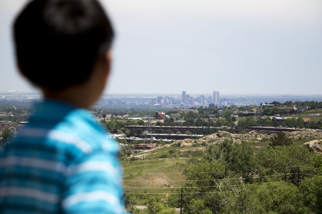 Andrew Waskosky looks at Denver out in the distance while on a tour of Magic Mountain, an archaeological dig site run by Michelle Koons of the Denver Museum of Nature and Science, June 22, 2018. (Kevin J. Beaty/Denverite)