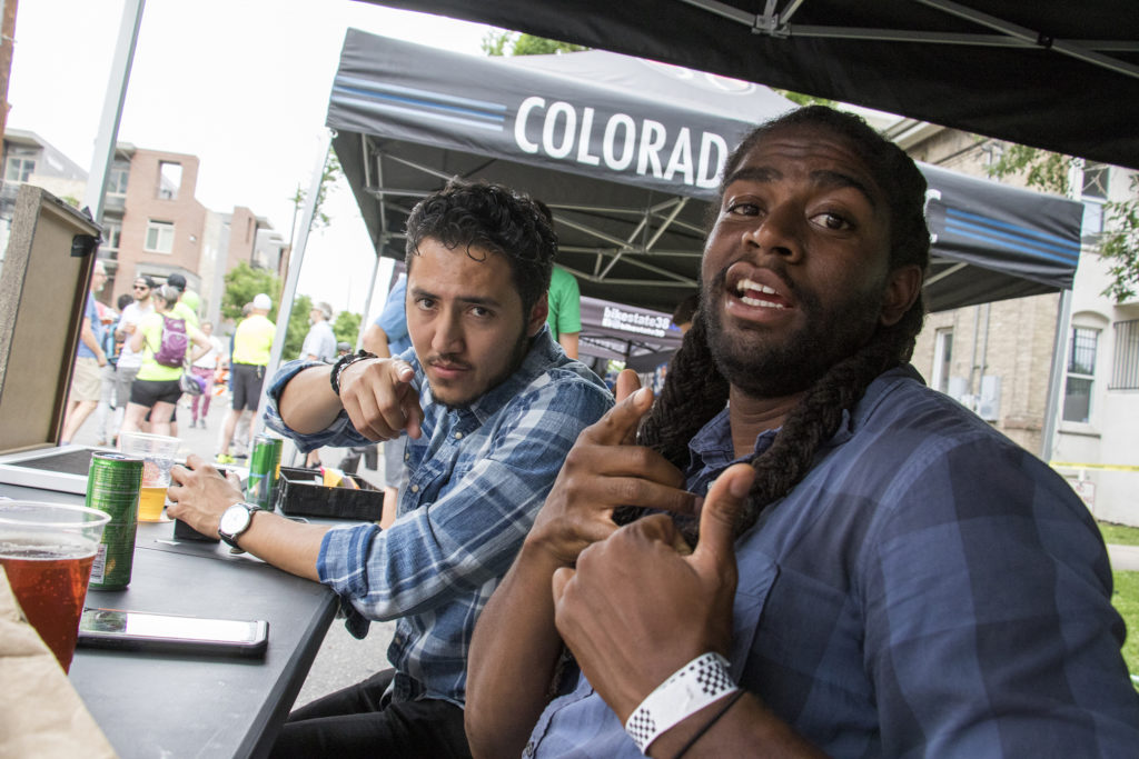 Denverite reporters Esteban L. Hernandez (left) and Allan Tellis man the Denverite booth at the Denverite Detour on Bike To Work Day, June 27, 2018. (Kevin J. Beaty/Denverite)
