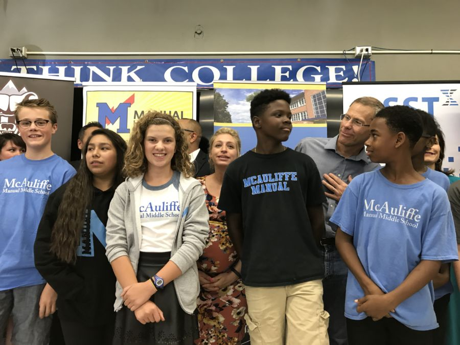 McAuliffe Manual students gather for a photo with Denver Public Schools officials at a press conference in 2017. (Melanie Asmar/Chalkbeat)