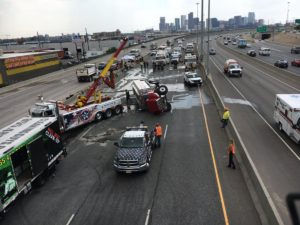A towing crew works to remove an overturned tanker truck from Interstate 25 northbound. (CDOT)