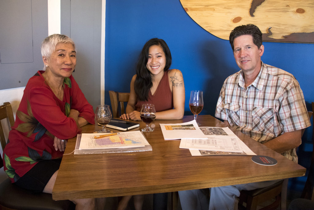 Stella Yu (left to right), Ann Nguyen and David Riggs, members of the La Alma-Lincoln Park Neighborhood Association, pose for a portrait over a beer at The Intrepid Sojourner Beer Project on 8th Avenue, July 3, 2018. (Kevin J. Beaty/Denverite)