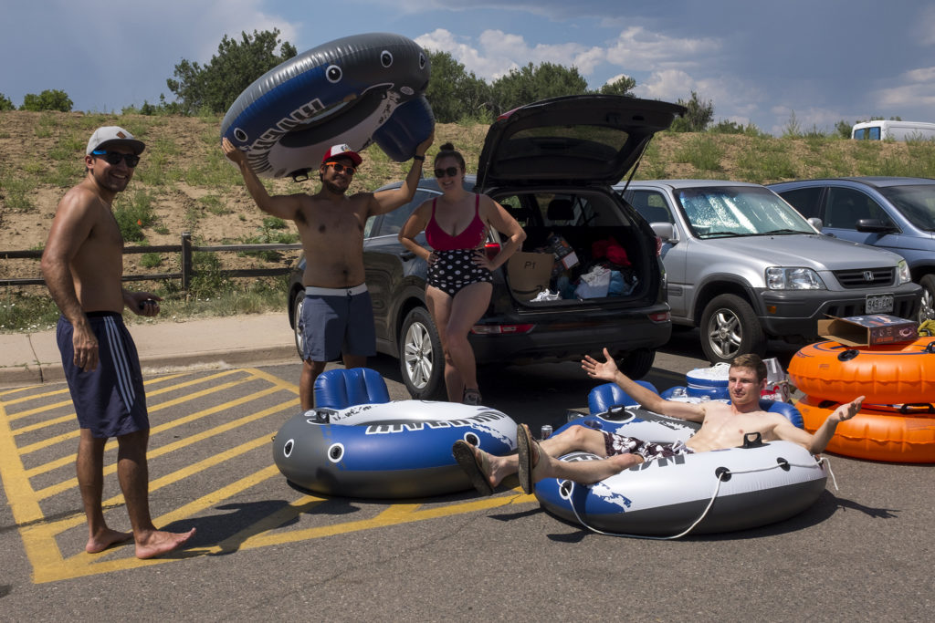 Leo Aubone (left to right), Alfonso Diaz, Megan Lake and Steve Wilk ponder what to do next now that they know the South Platte River is very low for tubing this year. South Platte Park in Littleton, July 4, 2018. (Kevin J. Beaty/Denverite)
