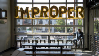 """Kevin Patrick, who says he's """"probably"""" improper, hangs out during Improper City's soft opening in RiNo. Five Points, July 9, 2018. (Kevin J. Beaty/Denverite)"""