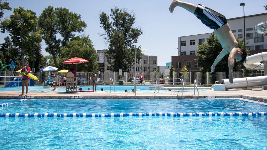 Lifeguard Marina Luna keeps an eagle eye over the pool as Anthem, who is 14, takes a dive. The La Alma Recreation Center, July 11, 2018. (Kevin J. Beaty/Denverite)