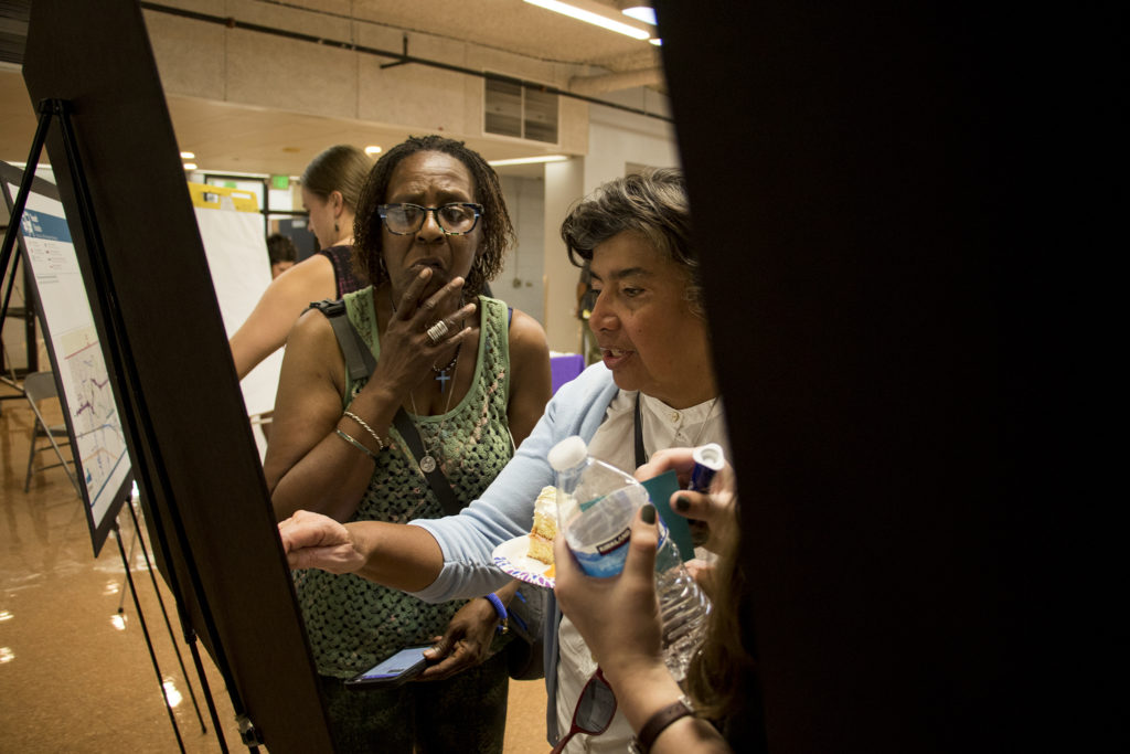 Pam Jiner (left) and Loretta Pineda inspect a map during a comment session on the Far Northeast Area Plan. Montbello campus cafeteria, July 12, 2018. (Kevin J. Beaty/Denverite)