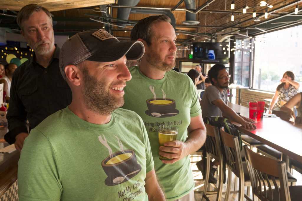 Chris Lombardi (left) and Rob Toftness wait with bated breath as The Cherry Cricket's chile cookoff results are read, July 19, 2018. (Kevin J. Beaty/Denverite)