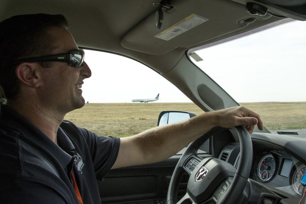 Levi Hosdon, a USDA wildlife manager, drives around Denver International Airport's airfield, July 19, 2018. (Kevin J. Beaty/Denverite)