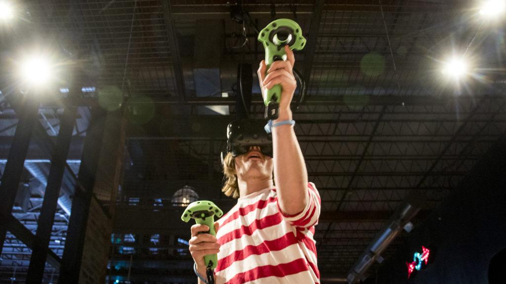 Trent Ripperda, a Waldo or virtual realtity ambassador at Punch Bowl Social Broadway, plays Space Pirates on July 18, 2018. (Kevin J. Beaty/Denverite)