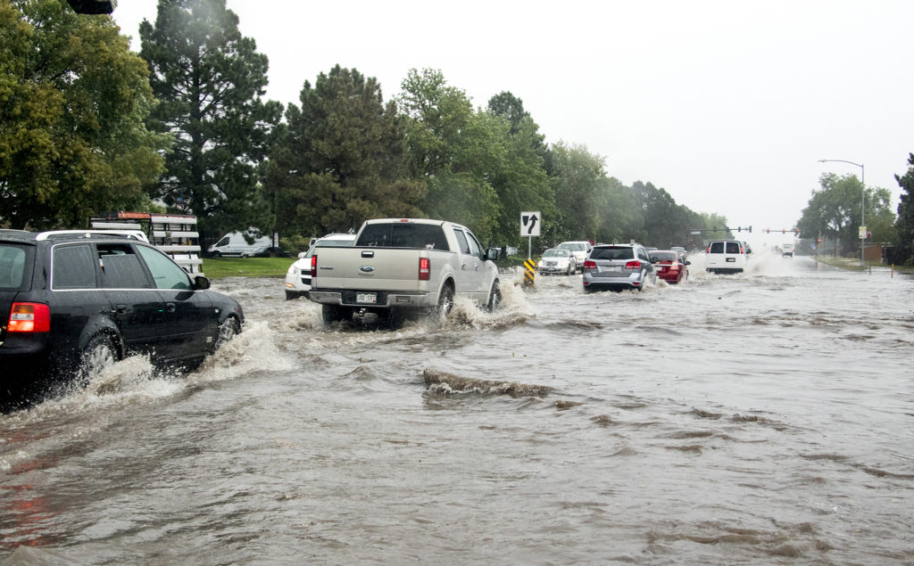 Cars attempt to drive north on Peoria Street as a massive rainstorm causes flooding in Montbello, July 23, 2018. (Kevin J. Beaty/Denverite)