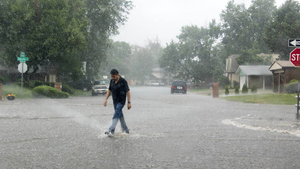 A man crosses Andrews Drive as a massive rainstorm causes flooding in Montbello, July 23, 2018. (Kevin J. Beaty/Denverite)