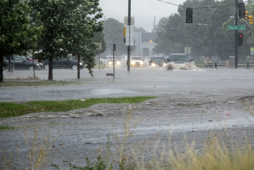 Vehicles cross Peoria Street as a massive rainstorm causes flooding in Montbello, July 23, 2018. (Kevin J. Beaty/Denverite)
