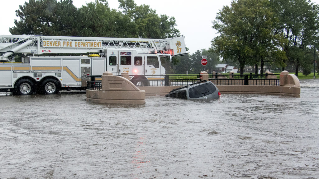A vehicle sunk into a drainage ditch at Andrews and Tulsa Courts as a massive rainstorm causes flooding in Montbello, July 23, 2018. (Kevin J. Beaty/Denverite)
