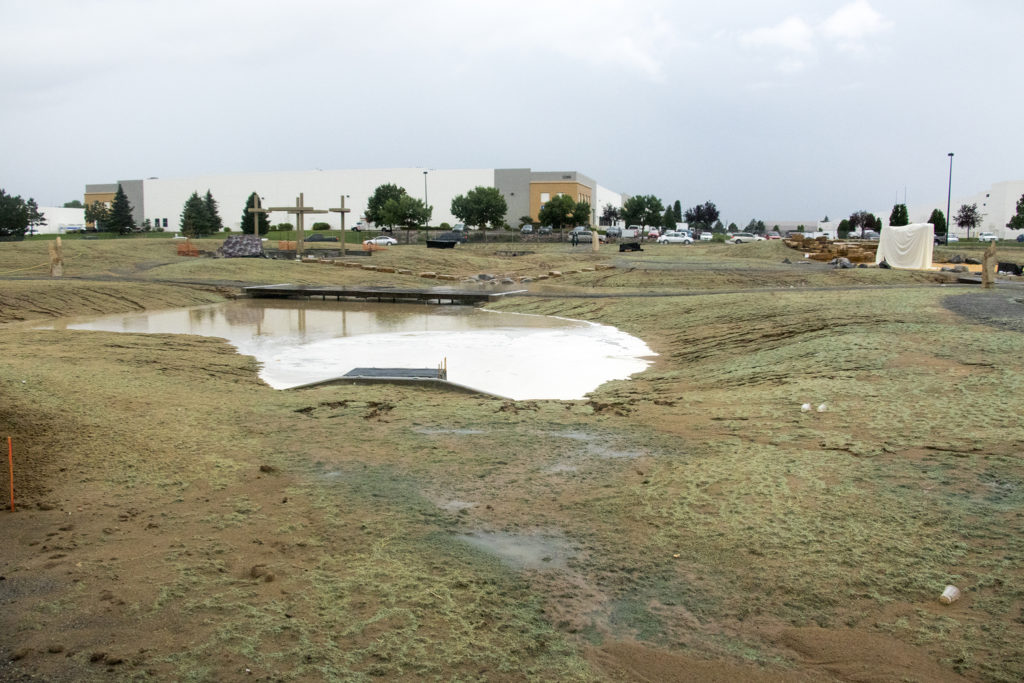 A flood control system got an accidental test at Montbello Open Space Park after the unveling of a new climbing wall (still under a veil, to the right) was cancelled due to  massive rainstorm, July 23, 2018. (Kevin J. Beaty/Denverite)