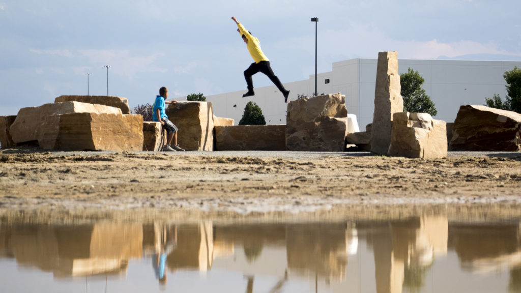 Dom Martinez, 15, hops over a boulder. A new climbing boulder is unveiled at Montbello Open Space Park, July 24, 2018. (Kevin J. Beaty/Denverite)