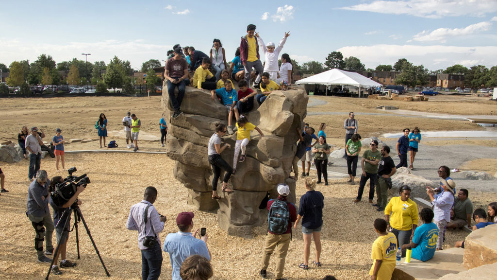 Kids climb atop a new boulder unveiled at Montbello Open Space Park, July 24, 2018. (Kevin J. Beaty/Denverite)