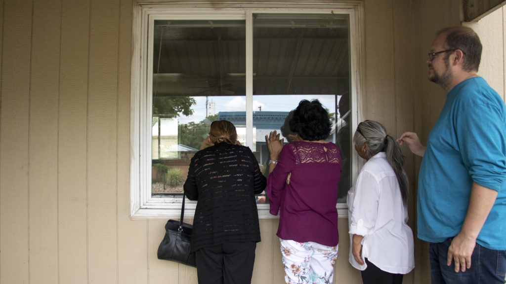Mercedes Gonzalez (left to right), Maria De Luna Jimenez, Angelina Torres and Robin Reichhardt peer into a house acquired by the GES Coalition Organizing for Health and Housing Justice in Elyria Swansea to help shield residents from displacement, July 26, 2018. (Kevin J. Beaty/Denverite)
