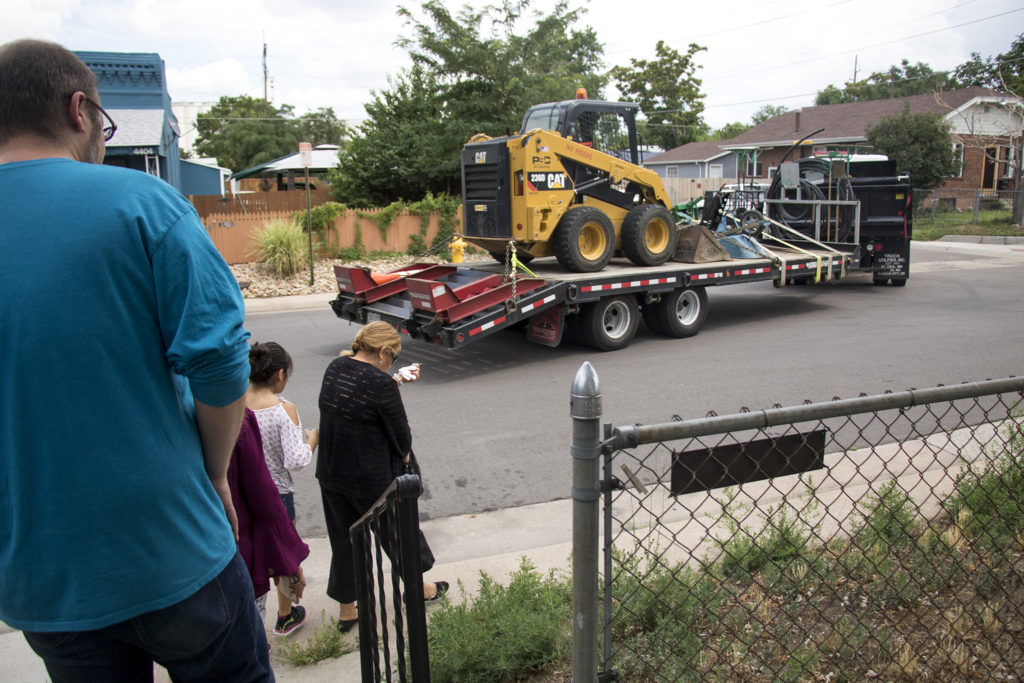 Members of the GES Coalition Organizing for Health and Housing Justice walk around a home they acquired in Elyria Swansea to help shield residents from displacement as construction equipment rolls by, July 26, 2018. (Kevin J. Beaty/Denverite)