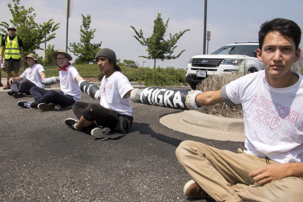 Colin Moore (left to right), Jamie, Richard and Daniel, who preferred not to give their last names, block the entrance to the Jim Bailey Building, local headquarters for U.S. Immigrations and Customs Enforcement in Centennial, Aug. 2, 2018. (Kevin J. Beaty/Denverite)