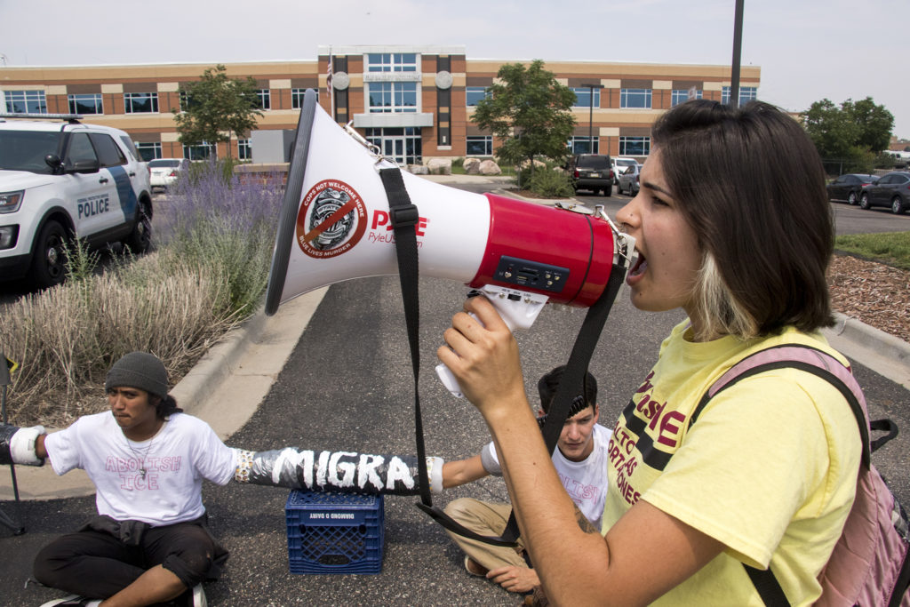 Megan Ferreira leads chants. Immigration activists rally in front of the Jim Bailey Building, local headquarters for U.S. Immigrations and Customs Enforcement in Centennial, Aug. 2, 2018. (Kevin J. Beaty/Denverite)