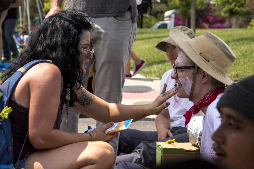 Megan Meyer applies sunscreen on an activist named Jamie's face as he and other activists create a human blockade in front of the Jim Bailey Building, local headquarters for U.S. Immigrations and Customs Enforcement in Centennial, Aug. 2, 2018. (Kevin J. Beaty/Denverite)