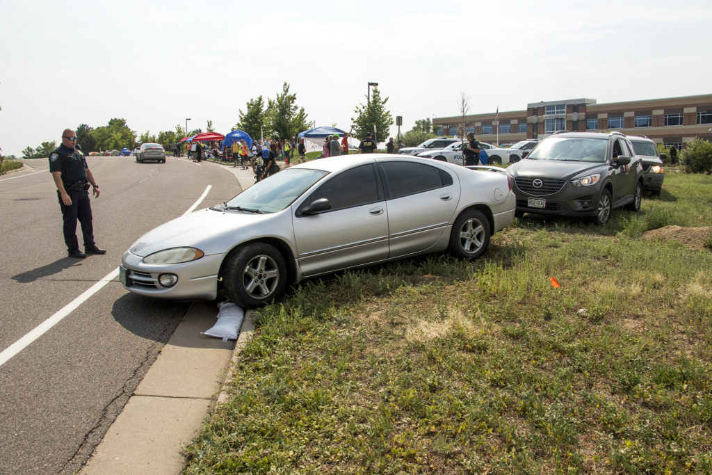 Despite protesters' blockade efforts, U.S. Immigrations and Customs Enforcement employees were able to leave work around them, Aug. 2, 2018. (Kevin J. Beaty/Denverite)