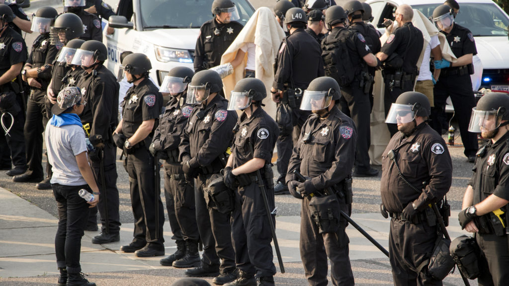 Police surround immigration activists who blockaded the local headquarters for U.S. Immigrations and Customs Enforcement in Centennial, Aug. 2, 2018. (Kevin J. Beaty/Denverite)