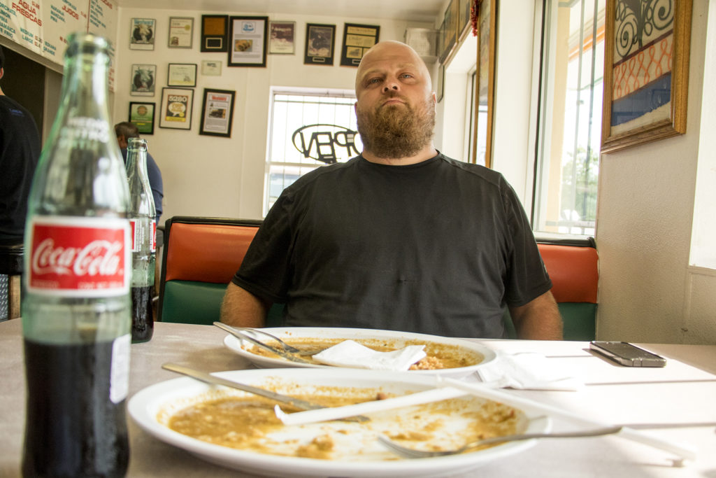 Brian Muehl poses for a portrait over his cleaned plate at El Taco De Mexico on Santa Fe Drive, Aug. 6, 2018. (Kevin J. Beaty/Denverite)