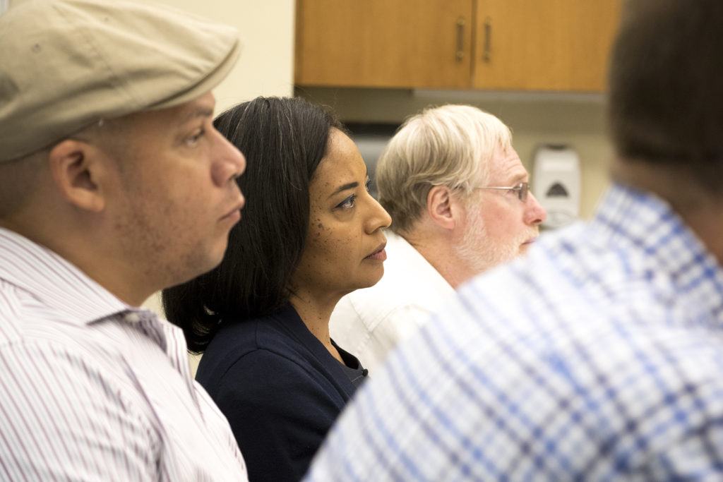 Lisa Calderón listens as Denver Police Chief Paul Pazen presents his department's new use-of-force policy to a room of community stakeholders at the Blair-Caldwell African American Research Library, Aug. 6, 2018. (Kevin J. Beaty/Denverite)