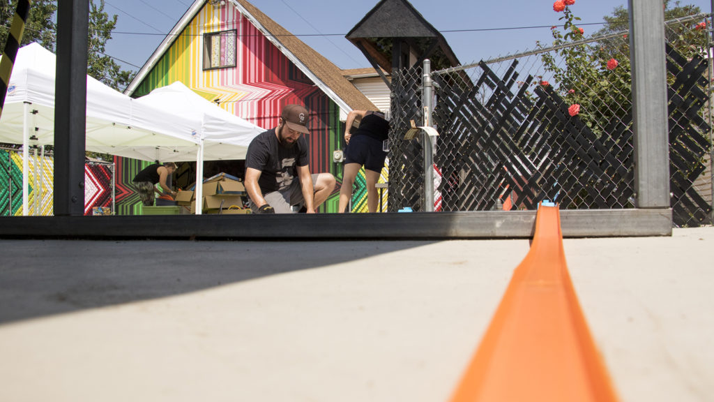 """Brian Colonna sets up Hot Wheels car tracks around """"This Machine Has A Soul,"""" an art installation by Warm Cookies of the Revolution meant to get people thinking about participatory budgeting, Aug. 15, 2018. (Kevin J. Beaty/Denverite)"""