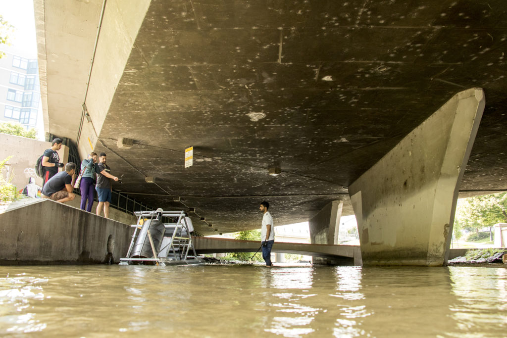 Professor Rafael Sanchez leads a group of University of Colorado Denver engineering students to test their first model of a trash-eating water wheel on the Cherry Creek, Aug. 20, 2018. (Kevin J. Beaty/Denverite)