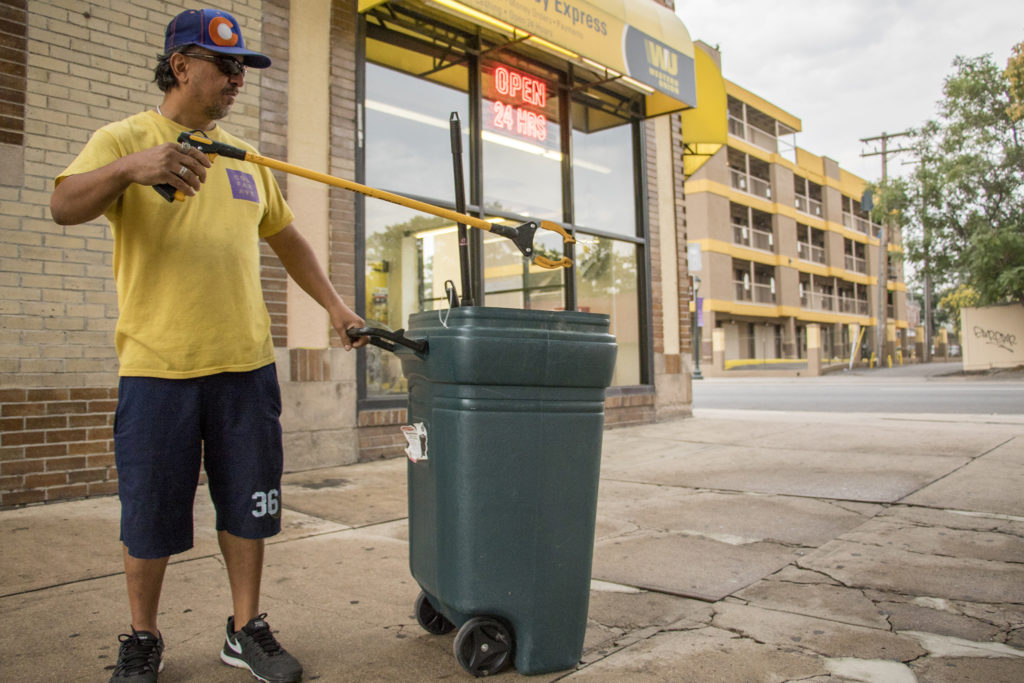Chris Trujullo, who has struggled to keep a job after a car crash left him with a serious brain injury, picks up trash as part of his job with Colfax Works. North Capitol Hill, Aug. 24, 2018. (Kevin J. Beaty/Denverite)