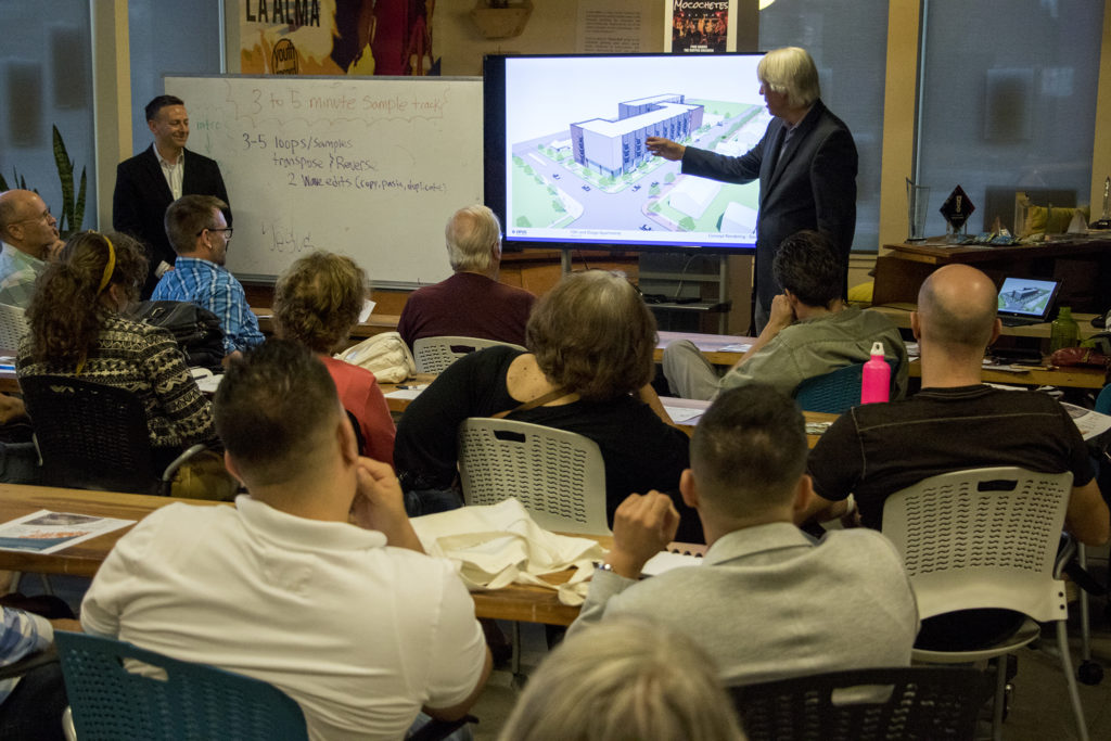 Senior vice president of Opus development group, Dean Newins, presents very tentative ideas of a possible new development at 13th Avenue and Osage Age during the La Alma Lincoln Park Neighborhood Association monthly meeting at Youth on Record, Aug. 22, 2018. (Kevin J. Beaty/Denverite)