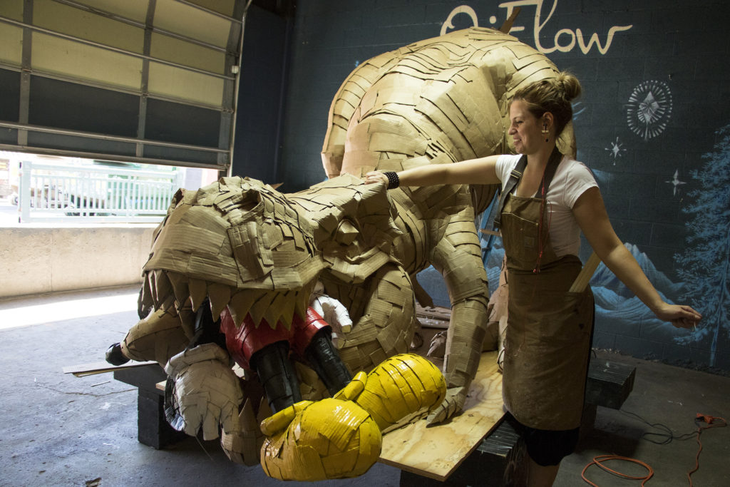 Laurence Vallieres makes a giant cardboard T-Rex eating a familiar cartoon mouse for Colorado Crush. RiNo, Five Points, Aug. 29, 2018. (Kevin J. Beaty/Denverite)