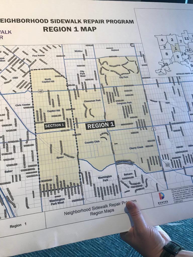 Matt Bryner, acting director of right-of-way services, holds up a poster showing a map of the Region 1 sidewalk repair program. (Esteban L. Hernandez / Denverite)