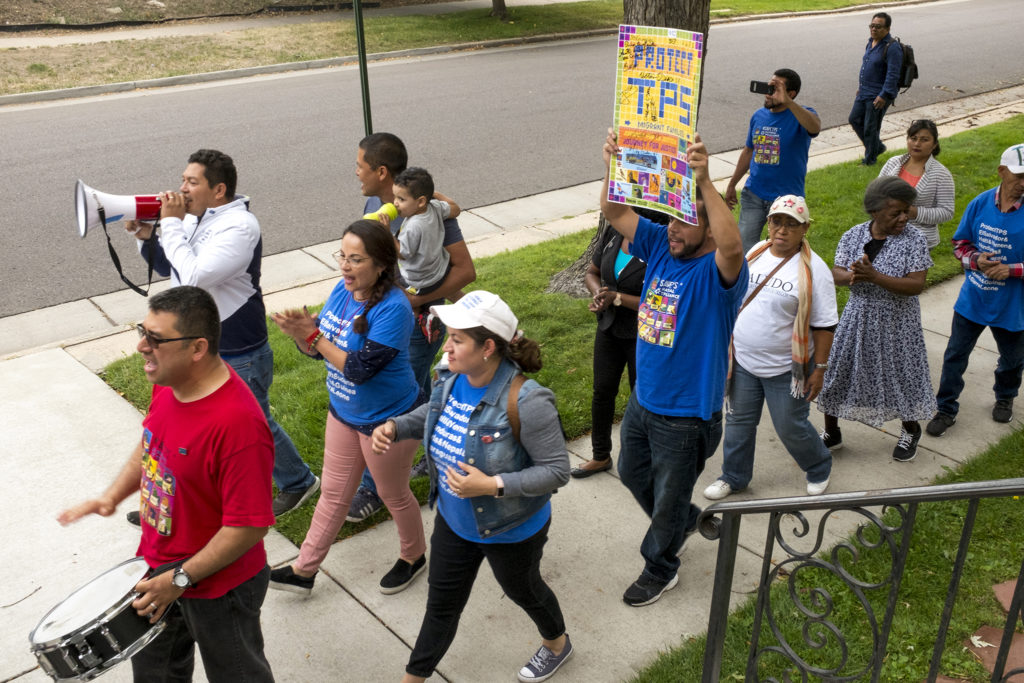A roadtripping group of protesters, fighting for status to remain in the U.S., arrive at Park Hill United Methodist Church where Araceli Velasquez has lived in sanctuary for 13 months. Her husband, Jorge, will soon lose Temporary Protected Status to remain in the country legally, along with many more migrants from El Salvador and a handful of other countries, Sept. 3, 2018. (Kevin J. Beaty/Denverite)