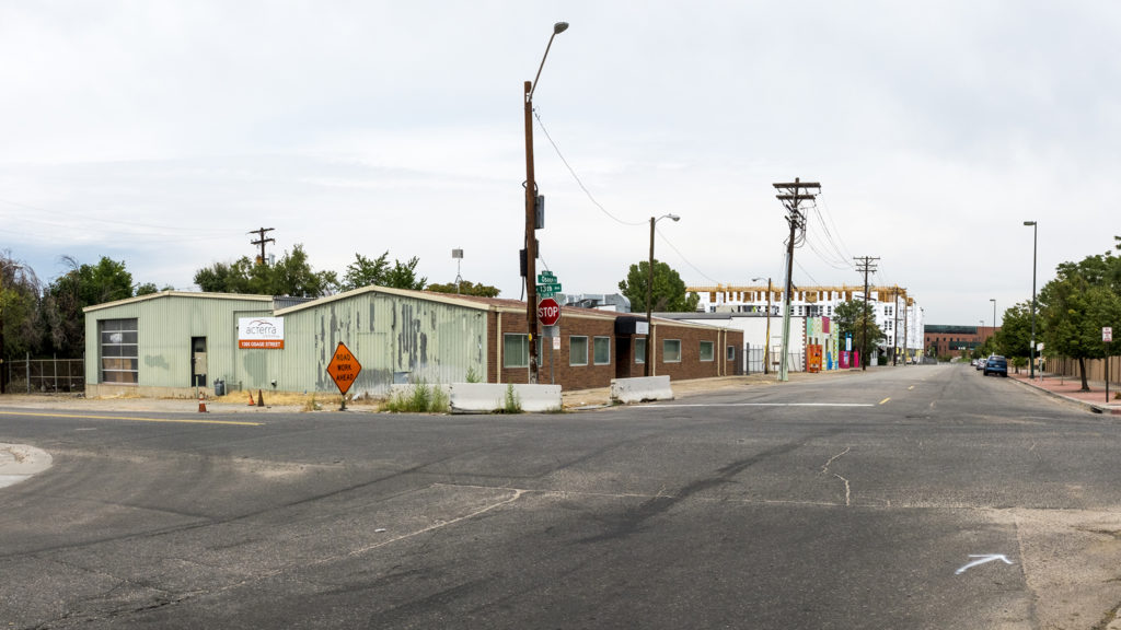 A vacant part of a lot that developers Opus Group are considering for an apartment building (left) and the Wellington Apartments on Osage Street south of Colfax Avenue, Sept. 3, 2018. (Kevin J. Beaty/Denverite)