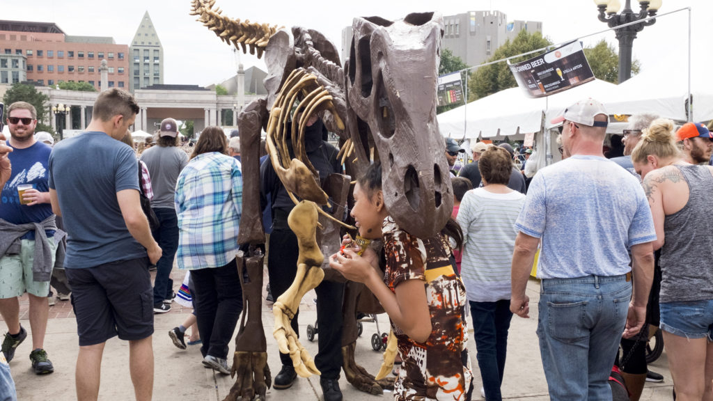 """Yaysayra, 13, gets eaten by Tim Seeber, AKA """"Mr. Bones,"""" in his homemade T-Rex outfit during Taste of Colorado at Civic Center Park, Sept. 3, 2018. (Kevin J. Beaty/Denverite)"""