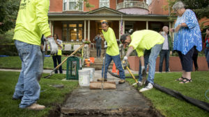 Workers with Ruben Rivera LLC (that's him in the middle) level out flagstone slabs in front of Diane Travis' 126-year-old home in North Capitol Hill. That's Travis on the right watching. Sept. 5, 2018. (Kevin J. Beaty/Denverite)
