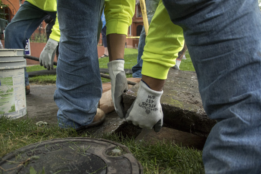 Workers with Ruben Rivera LLC level out flagstone sidewalks in front of Diane Travis' 126-year-old home in North Capitol Hill, Sept. 5, 2018. (Kevin J. Beaty/Denverite)