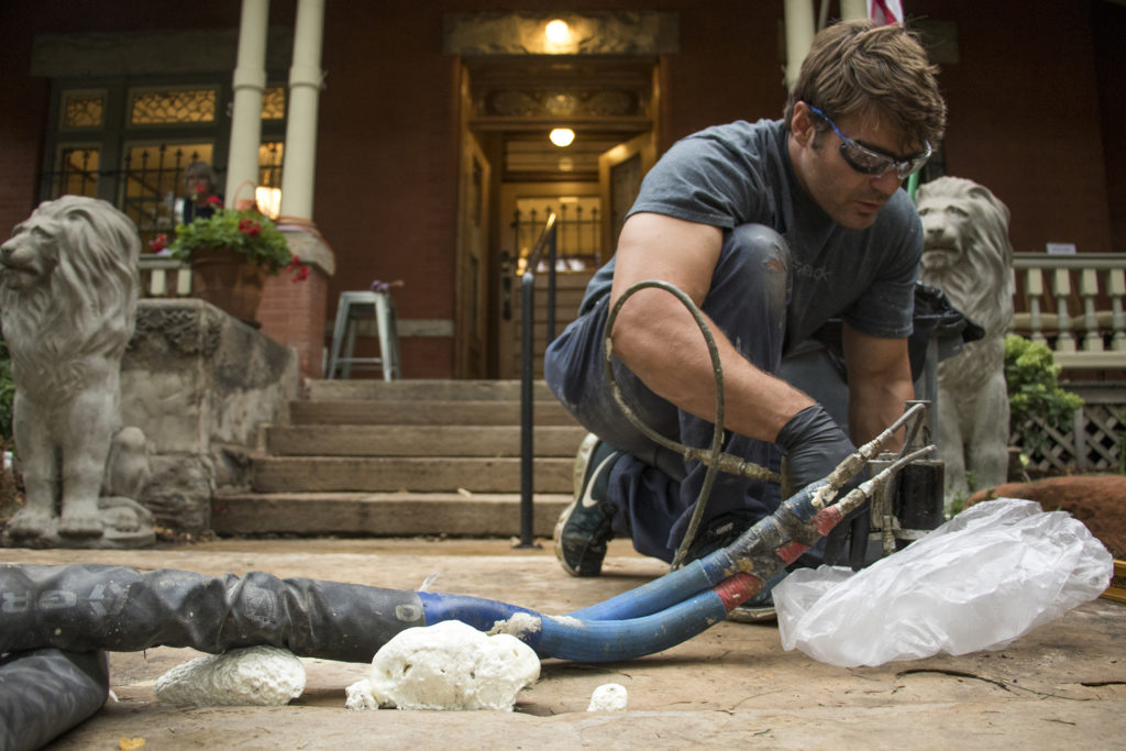 CreteJack worker Brent O'Toole injects polyurethane beneath a flagstone slab in front of Diane Travis' 126-year-old home in North Capitol Hill. You can see the foam rising up through the cracks on the left. Sept. 5, 2018. (Kevin J. Beaty/Denverite)
