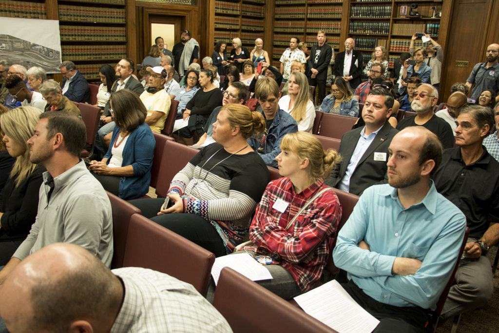 The Parr-Widener Community Room was standing-room only at the start of the hearing. The Denver Board of Public Health and Environment holds a special hearing on a request for the I-70 expansion project to breach normal legal limits on noise pollution, Sept. 6, 2018. (Kevin J. Beaty/Denverite)