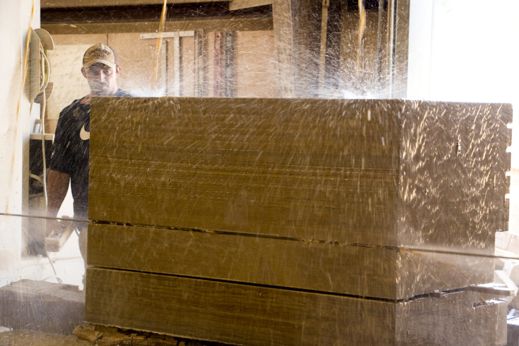 Scott Moore watches as stone slabs are cut by a massive cable saw. Lyons Sandstone, Sept. 7, 2018. (Kevin J. Beaty/Denverite)
