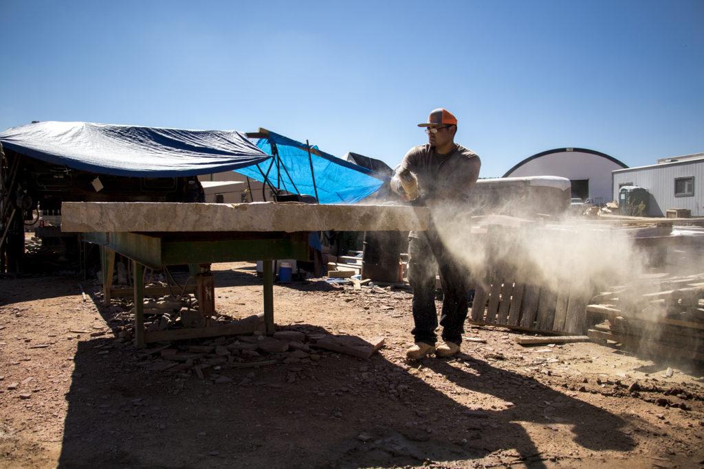 Matt Lewis sweeps dust off a large slab at Lyons Sandstone, Sept. 7, 2018. (Kevin J. Beaty/Denverite)