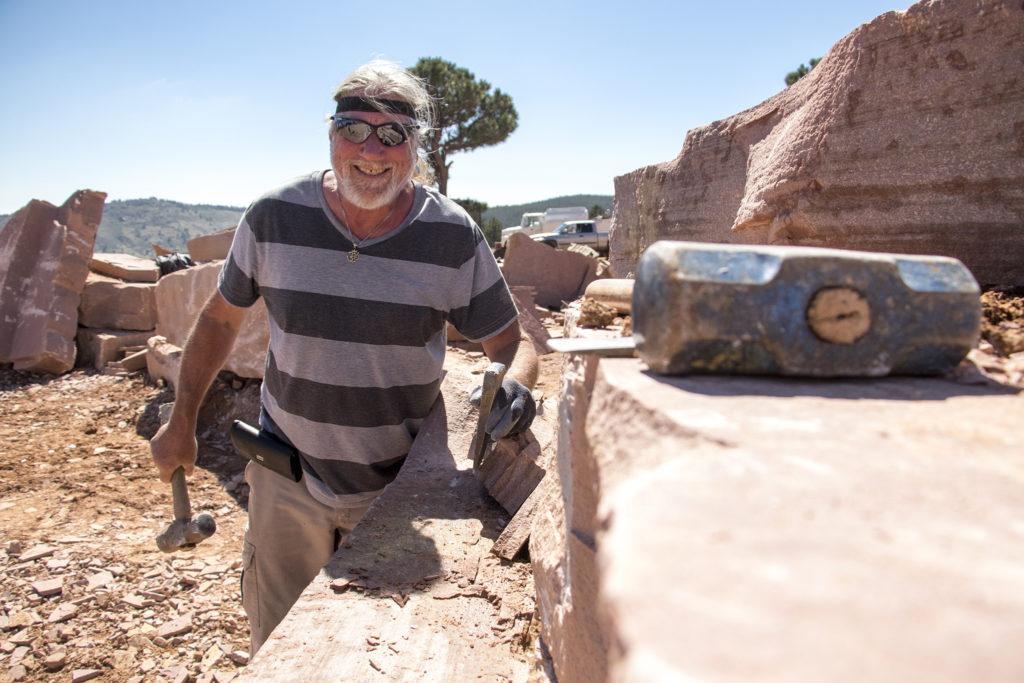 Jow Amer hammers slabs out of a large boulder at Lyons Sandstone, Sept. 7, 2018. (Kevin J. Beaty/Denverite)